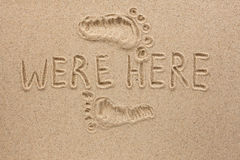 Word WERE HERE written on the sand Stock Photo