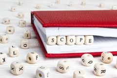 Word Werkingsgebied in houten blokken in rood notitieboekje op witte houten lijst wordt geschreven die royalty-vrije stock foto