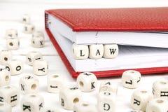 Word Wet in houten blokken in rood notitieboekje op witte woode wordt geschreven die Stock Foto