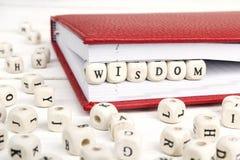 Word Wijsheid in houten blokken in rood notitieboekje op witte wo wordt geschreven die Stock Fotografie