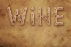 Word wine shaped by corks on brown paper parchment. Word WINE shaped by natural wooden wine bottle corks of different vintage years over background of brown Royalty Free Stock Photo