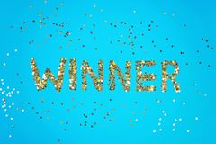 The word Winner is laid out of starry confetti on a blue background. royalty free stock photography