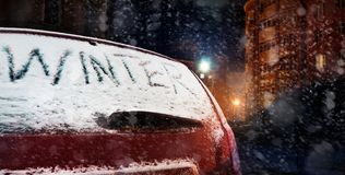 Word winter on car, outside at night, concept of cold winter, dangerous ice road Stock Photo