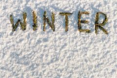 Word winter composed of fir branches in the snow. The word winter composed of fir branches in the snow royalty free stock photo