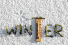 Word winter from fir branches. Thermometer with sub-zero temperatures in the snow in the winter. Word winter from fir branches royalty free stock photography