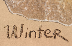 Word Winter is hand written on sand Royalty Free Stock Photography