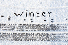Word winter and tire tracks in snow on road stock photo