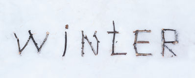 The word winter written with broken wooden sticks on snow backgr Royalty Free Stock Image