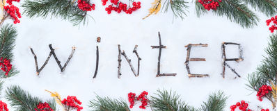 The word winter written with broken wooden sticks on snow backgr Stock Photo