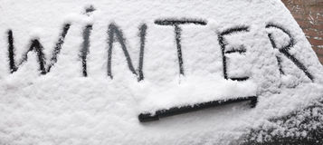Word Winter written on snowy rear screen car Stock Images