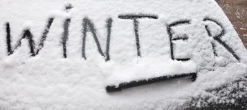 Word Winter written on snowy rear screen car. On the rear screen of a car the word Winter is written in the newly fallen snow stock images