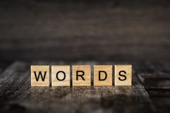 The word `words`. Made of bright wood cubes with black letters on a dark wooden background stock images