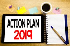 Word, writing Action Plan 2019. Business concept for Success Strategy Written on tablet laptop, wooden background with sticky note. Word, writing Action Plan Stock Photos