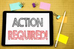 Word, writing Action Required. Business concept for Immediate Urgent Written on tablet laptop, wooden background with sticky note. Word, writing Action Required Royalty Free Stock Photos