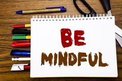Word, writing Be Mindful. Business concept for Mindfulness Healthy Spirit Written on notebook, wooden background with office equip. Word, writing Be Mindful Stock Image
