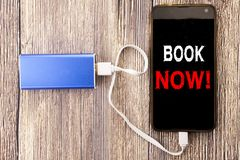 Word, writing Book Now. Business concept for Reservation Booking written on mobile cell phone mobile and power-bank charger on old royalty free stock photography