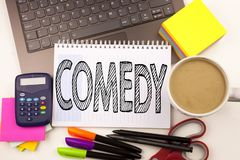 Word writing Comedy in the office with laptop, marker, pen, stationery, coffee. Business concept for Stand Up Comedy Microphone Wo. Rkshop white background with Stock Photography