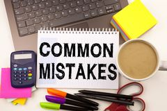 Word writing Common Mistakes in the office with surroundings such as laptop marker pen stationery coffee Business concept for Comm. On Decision Mistakes Workshop Stock Images