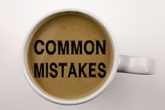 Word, writing Common Mistakes text in coffee in cup. Business concept for Common Decision Mistakes on white background with copy s Royalty Free Stock Photos