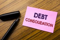 Word, writing Debt Consolidation. Business concept for Money Loan Credit Written on sticky note red paper, wooden background with. Word, writing Debt Stock Photo