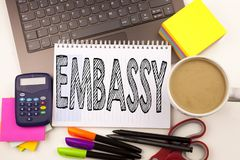 Word writing Embassy in the office with laptop, marker, pen, stationery, coffee. Business concept for Tourist Visa Application Wor. Kshop white background with Royalty Free Stock Image