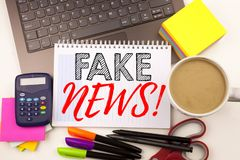Word writing Fake News in the office with laptop, marker, pen, stationery, coffee. Business concept for Propaganda Newspaper Fake. News Workshop white Royalty Free Stock Photos