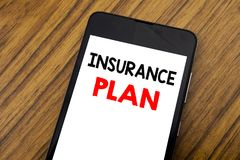 Word, writing handwriting Insurance Plan. Business concept for Health Life Insured Written on mobile phone cellphone, wooden backg. Word, writing handwriting Stock Photo