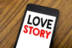 Word, writing handwriting Love Story. Business concept for Loving Someone Heart  Written on mobile phone cellphone, wooden backgro. Word, writing handwriting Royalty Free Stock Image