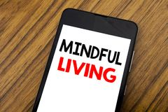 Word, writing handwriting Mindful Living. Business concept for Life Happy Awareness Written on mobile phone cellphone, wooden back. Word, writing handwriting Stock Images