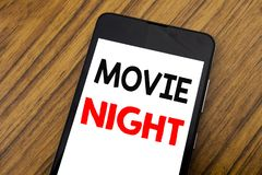 Word, writing handwriting Movie Night. Business concept for Wathing Movies Written on mobile phone cellphone, wooden background w. Word, writing handwriting royalty free stock image