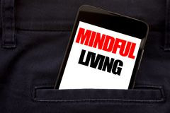 Word, writing Mindful Living. Business concept for Life Happy Awareness Written phone mobile phone, cellphone placed in the man fr. Word, writing Mindful Living Stock Photos