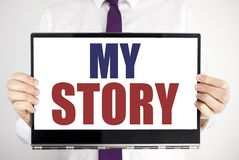 Word, writing My Story. Business concept for Telling Tell About You Written on tablet laptop holding by the man blurred background. Word, writing My Story Stock Photo