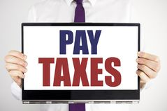 Word, writing Pay Taxes. Business concept for Taxation Overtax Return Written on tablet laptop holding by the man blurred backgrou. Word, writing Pay Taxes Stock Photography