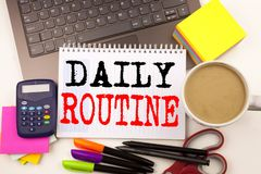 Word writing Daily Routine in the office with surroundings such as laptop marker pen stationery coffee Business concept for Accura Stock Image