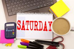 Word writing Saturday in the office with  laptop, marker, pen, stationery, coffee. Business concept for Happy Week Weekend Worksho. P white background with space Royalty Free Stock Images