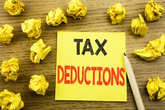 Word, writing Tax Deductions. Business concept for Finance Incoming Tax Money Deduction written on sticky note paper on the wooden. Word, writing Tax Deductions Royalty Free Stock Photography