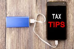 Word, writing Tax Tips. Business concept for Taxpayer Assistance Refund Reimbursement written on mobile cell phone mobile and powe. Word, writing Tax Tips stock photography