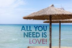 Word writing text All You Need Is Love Motivational. Business concept for Deep affection needs appreciation romance Blue beach wat. Er Thatched Straw Umbrellas Stock Photography
