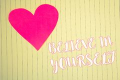 Word writing text Believe In Yourself. Business concept for Determination Positivity Courage Trust Faith Belief Light pink heart s. Ymbol white paper backstage stock images
