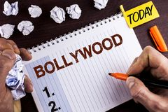 Word writing text Bollywood. Business concept for Indian cinema a source of entertainment written by Man on Notepad on wooden back. Word writing text Bollywood Stock Photos