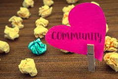 Word writing text Community. Business concept for Neighborhood Association State Affiliation Alliance Unity Group Clothespin holdi. Ng pink heart paper crumpled royalty free stock photo
