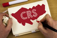 Word writing text Crs. Business concept for Common reporting standard for sharing tax financial information written by Man on Note. Word writing text Crs Royalty Free Stock Photography