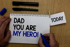 Word writing text Dad You Are My Hero. Business concept for Admiration for your father love feelings compliment Hand hold pen note. Pad with words paperclip grip royalty free stock photo