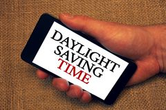 Word writing text Daylight Sayving Time. Business concept for advancing clocks during summer to save electricity Owner hold holdin. G smartphone white screen stock photo
