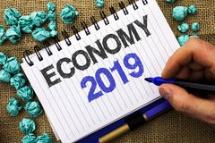 Word writing text Economy 2019. Business concept for Financial Currency Growth Market Earnings Trade Money written by Man Holding. Marker Notebook Book the jute Royalty Free Stock Photo