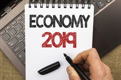 Word writing text Economy 2019. Business concept for Financial Currency Growth Market Earnings Trade Money written by Man Holding. Pen Notebook Book placed Royalty Free Stock Photos
