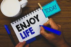 Word writing text Enjoy Life. Business concept for Any thing, place,food or person, that makes you relax and happy Man holding mar. Ker notebook clothespin royalty free stock photography
