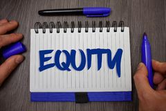 Word writing text Equity. Business concept for Value of a company divided into equal parts owned by shareholders Man hold holding. Blue marker notebook page stock image