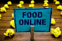 Word writing text Food Online. Business concept for asking for something to eat using phone app or website Clothespin holding blue. Paper note crumpled papers royalty free stock photos