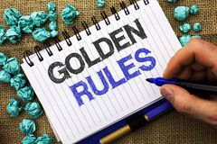 Word writing text Golden Rules. Business concept for Regulation Principles Core Purpose Plan Norm Policy Statement written by Man. Holding Marker Notebook Book Stock Image